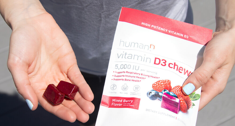 Person holding two D3 Chews and bag of D3 Chews