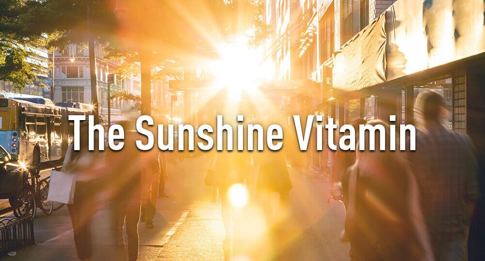Glare of the sun with people walking on sidewalk