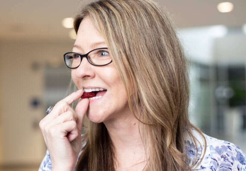 Woman with glasses putting a SuperBeets Heart Chew in her mouth